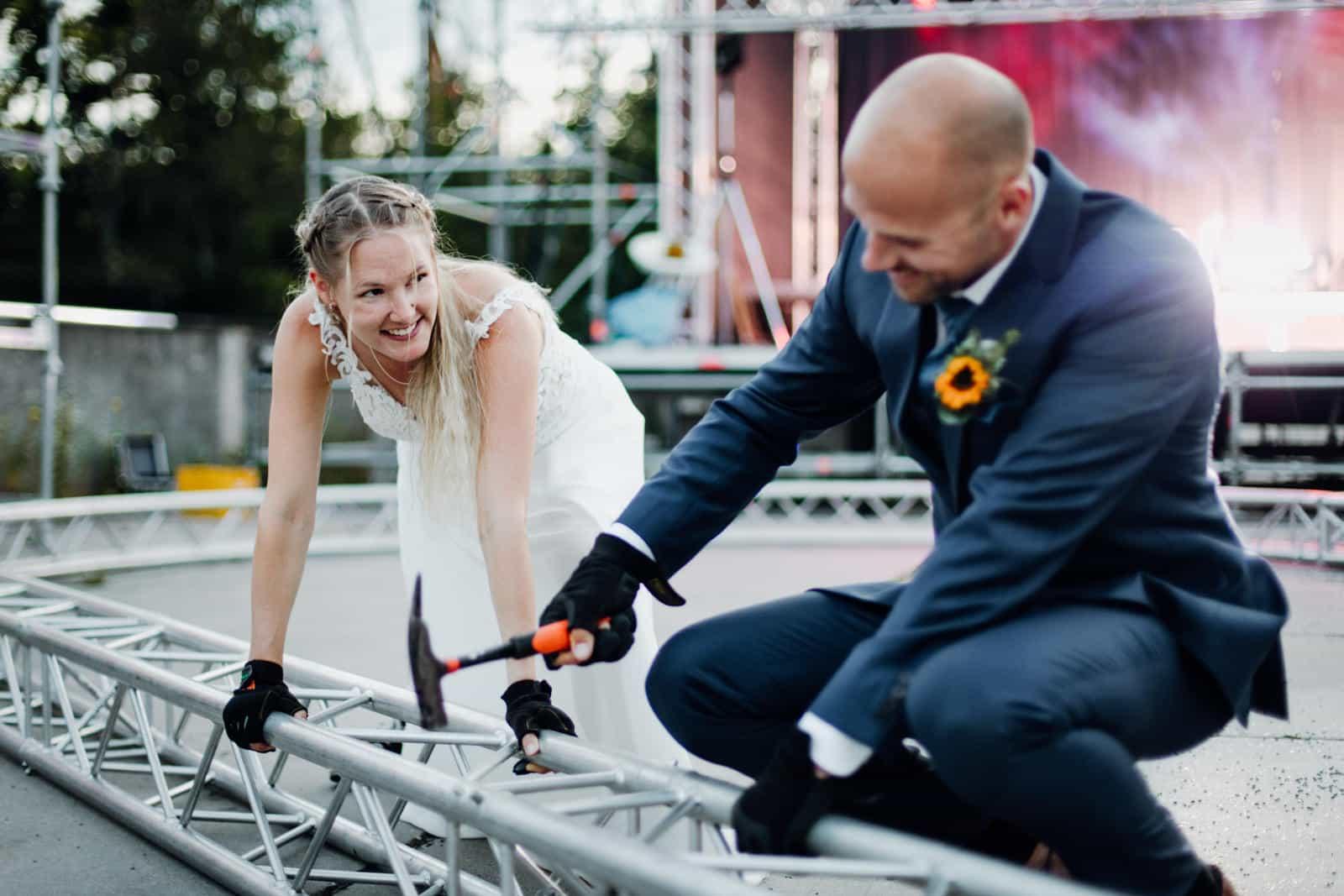 Brautpaar beim Fotoshooting vor einer Konzertbühne und nimmt Traversen auseinander.