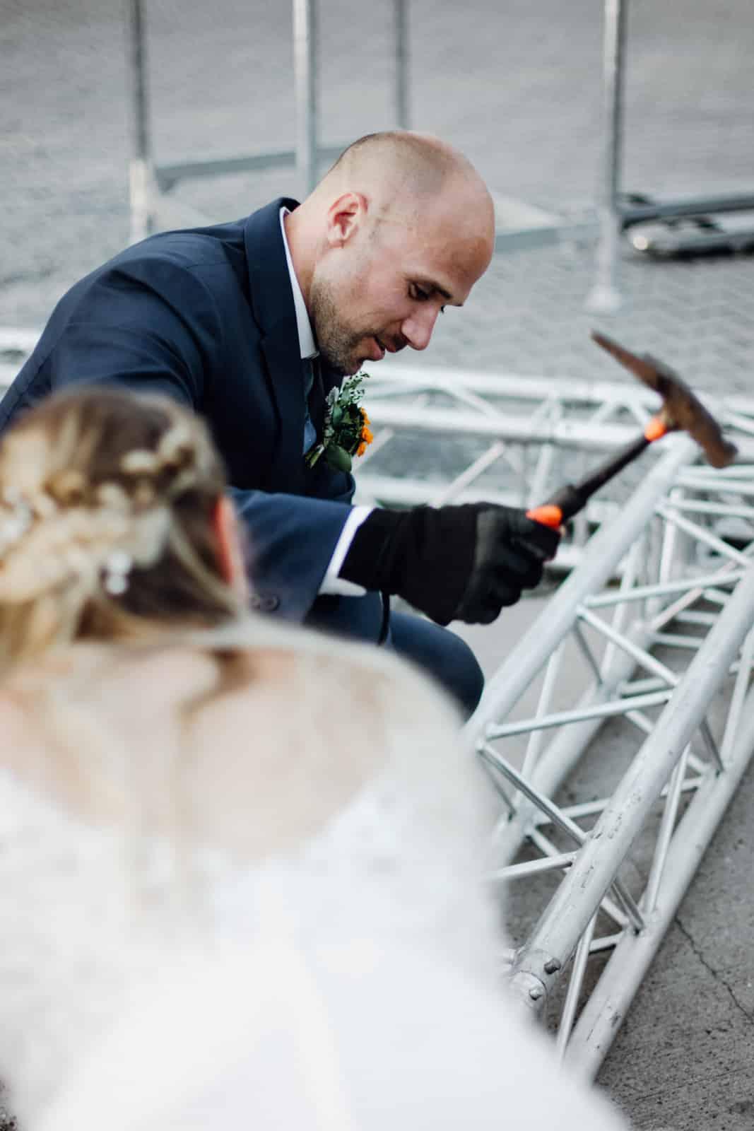 Bräutigam nimmt Traversen mit Hammer auseinander.