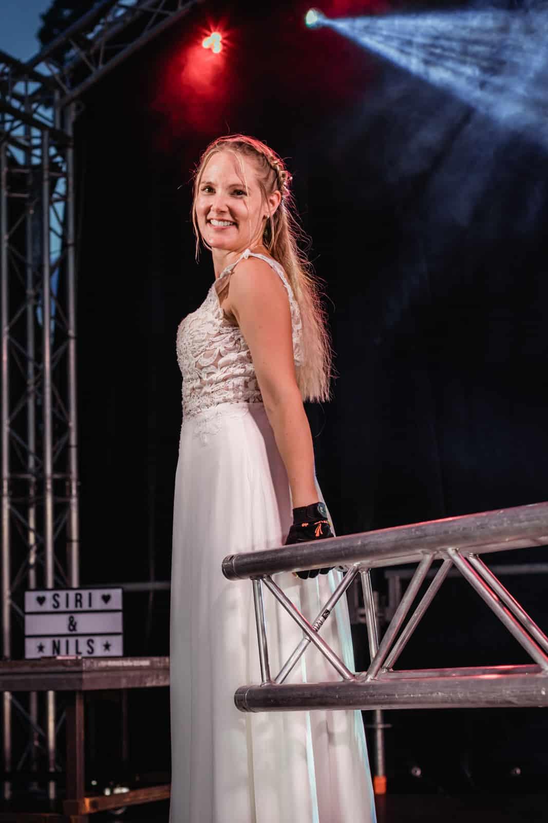 Braut steht auf Bühne bei Nacht und hält Traverse in Hand und schaut in die Kamera.