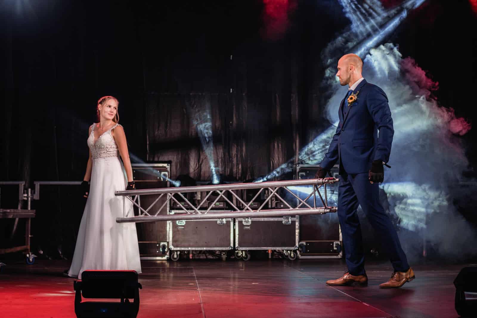 Brautpaar steht auf Bühne und hält Traverse in Hand und schaut sich an.