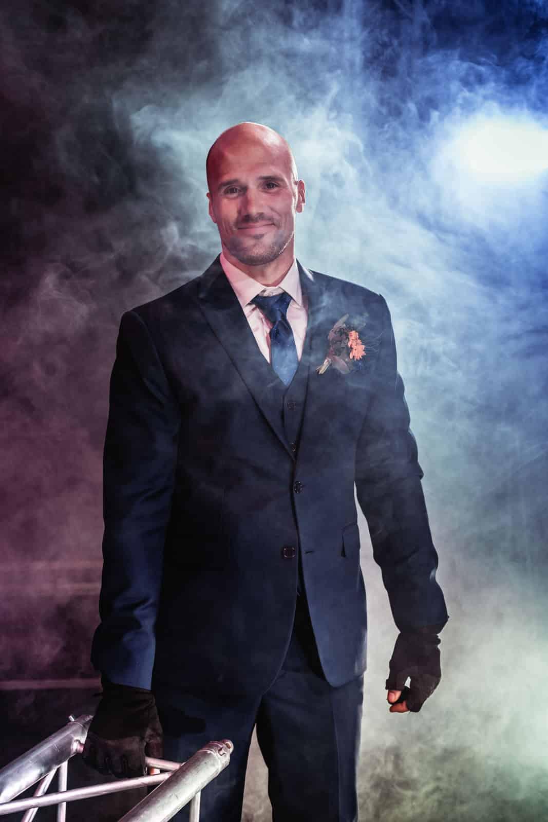 Mann im Anzug hält Traverse mit Arbeitshandschuhe auf ausgeleuchteter Bühne im Anzug.