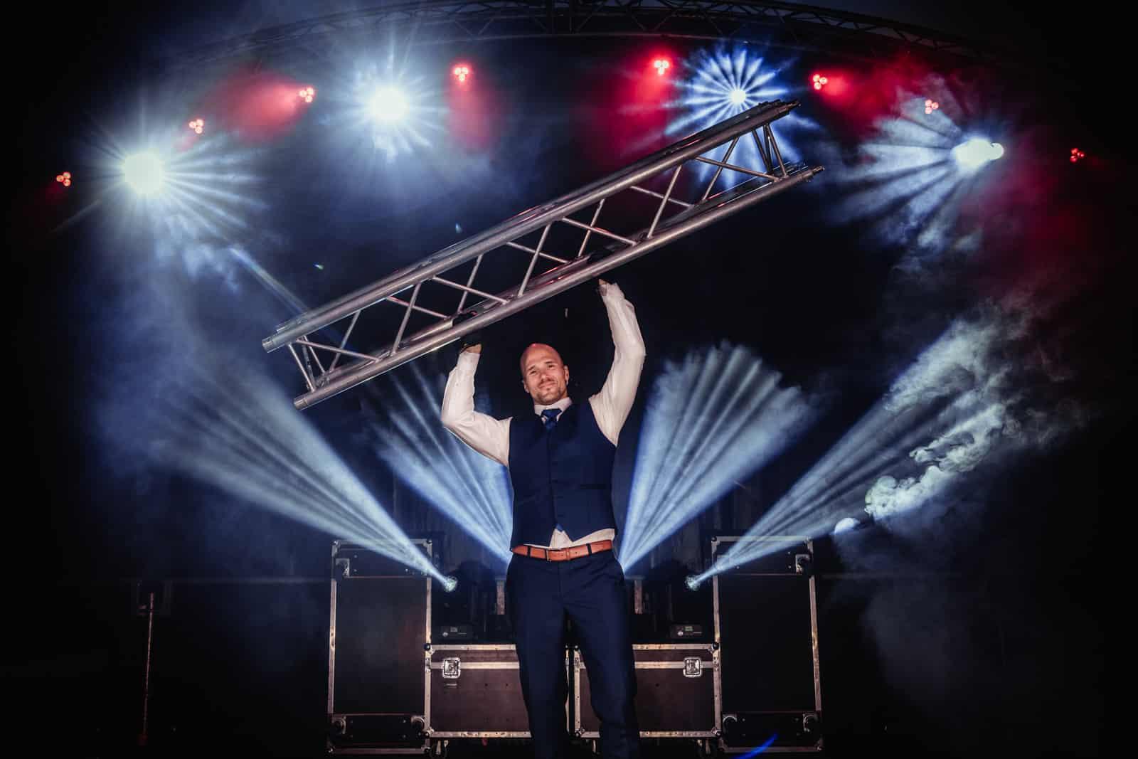 Mann hält eine Traverse über seinen Kopf hoch auf einer nächtlich beleuchteten Konzertbühne.