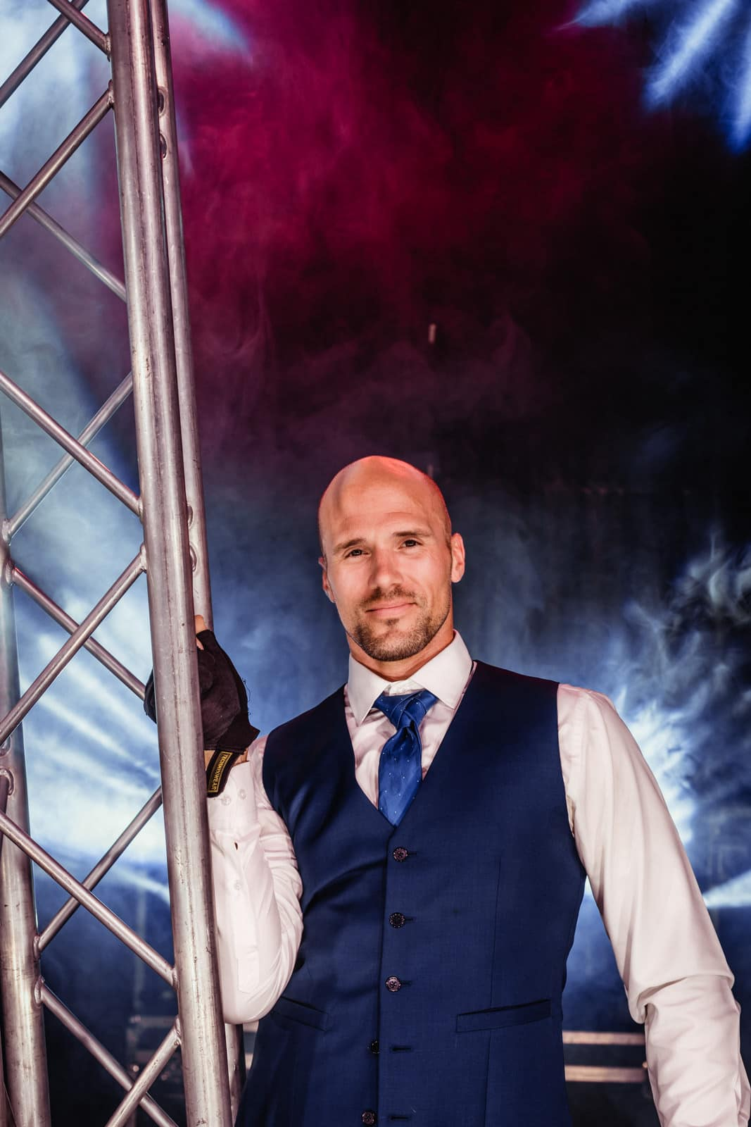 Mann hält im Hochzeitsoutfit und Arbeitshandschuhen eine Traverse in der rechten Hand auf einer Bühne bei Nacht.