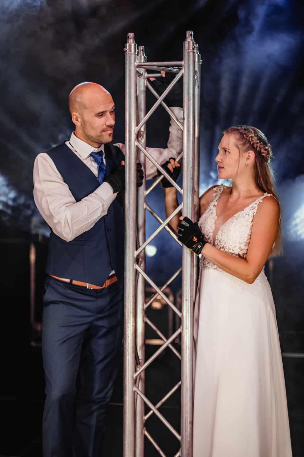 Brautpaar steht an einer Traverse mit Arbeitshandschuhen und schauen sich an.