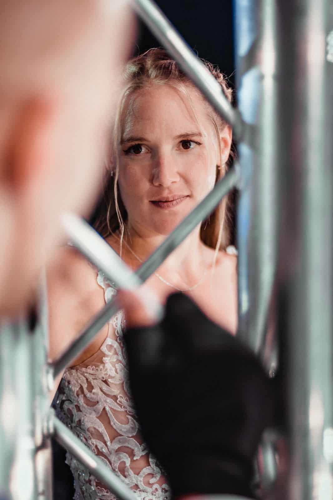 Frau schaut durch eine Traverse auf einer Bühne zu ihrem Mann