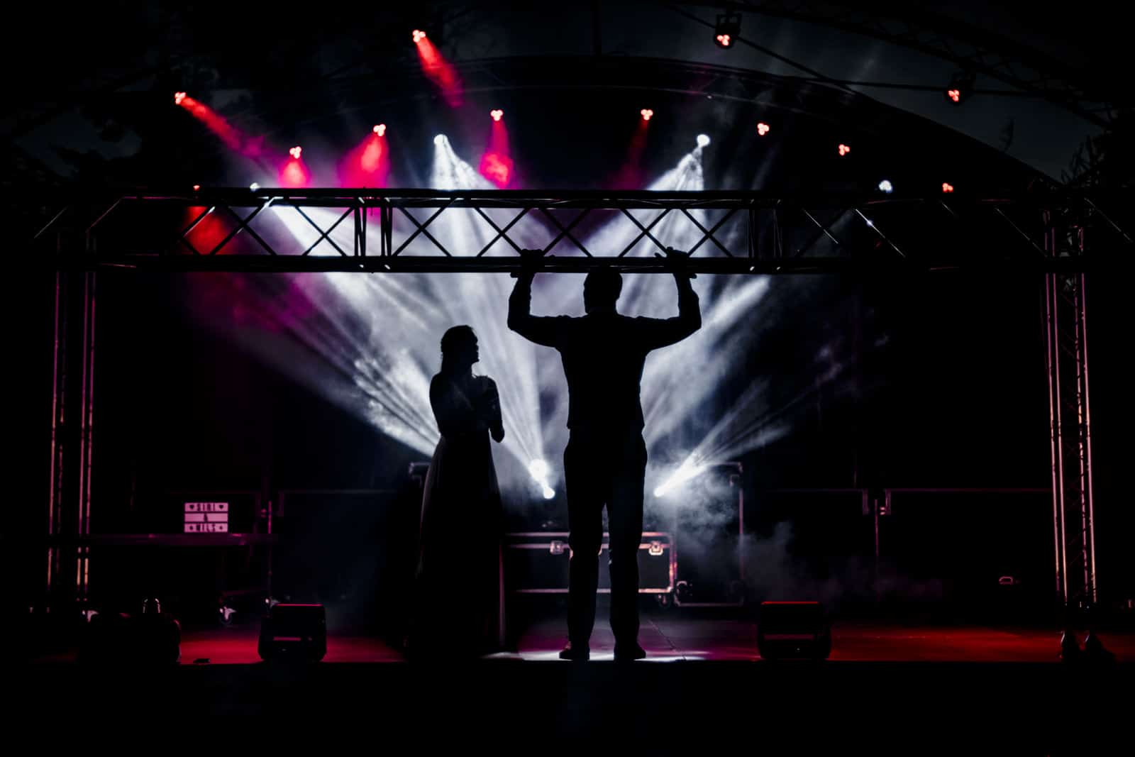 Bräutigam macht Klimmzug an Bühnentraverse und Braut schaut zu.