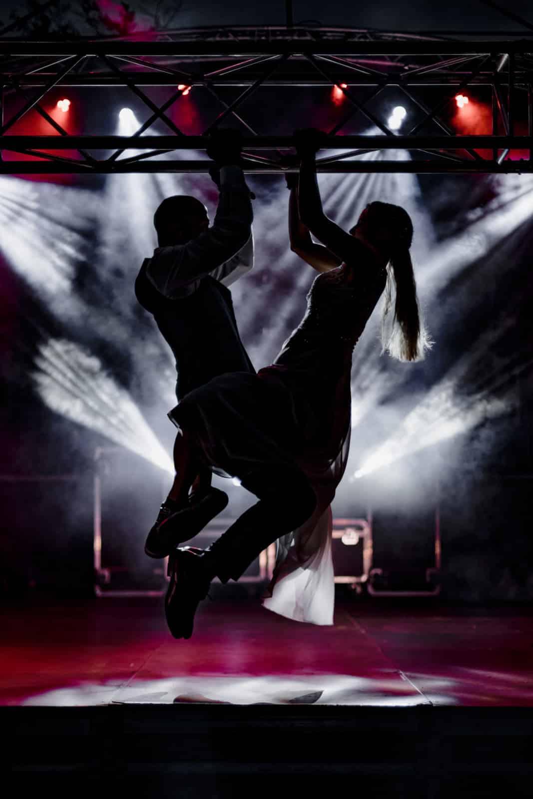 Brautpaar macht Klimmzüge als Silhouette an einer Traverse auf einer Bühne.