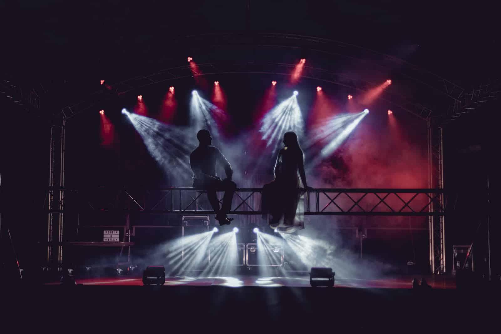 Brautpaar sitzt auf einer Traverse und schaut sich an als Silhouette und im Hintergrund sind Scheinwerfer in Strahlenform.