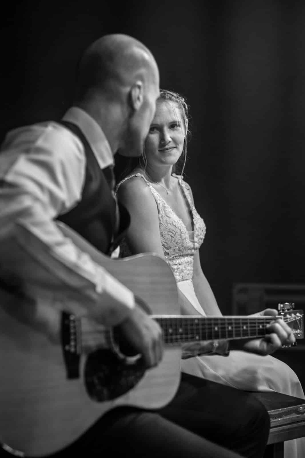 Braut schaut ihren Mann an der auf einer Gitarre auf einer Bühne zu ihr spielt.