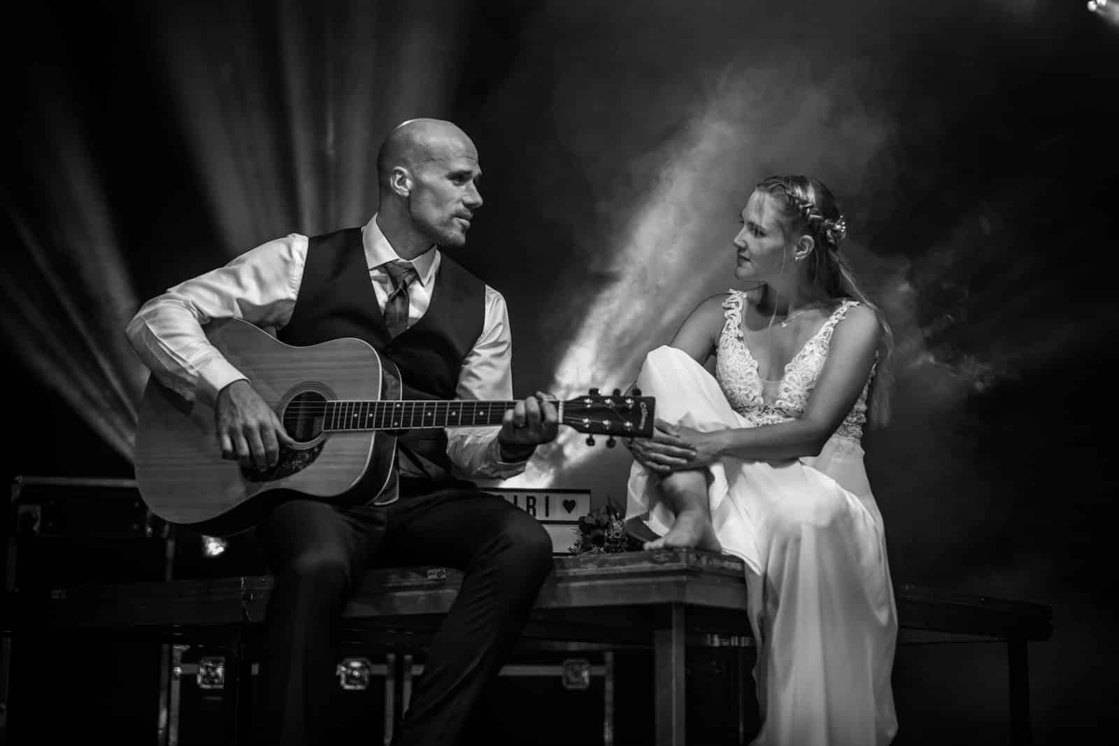 Braut hört ihrem Bräutigam zu während er ein Lied auf einer Gitarre zu ihr spielt.