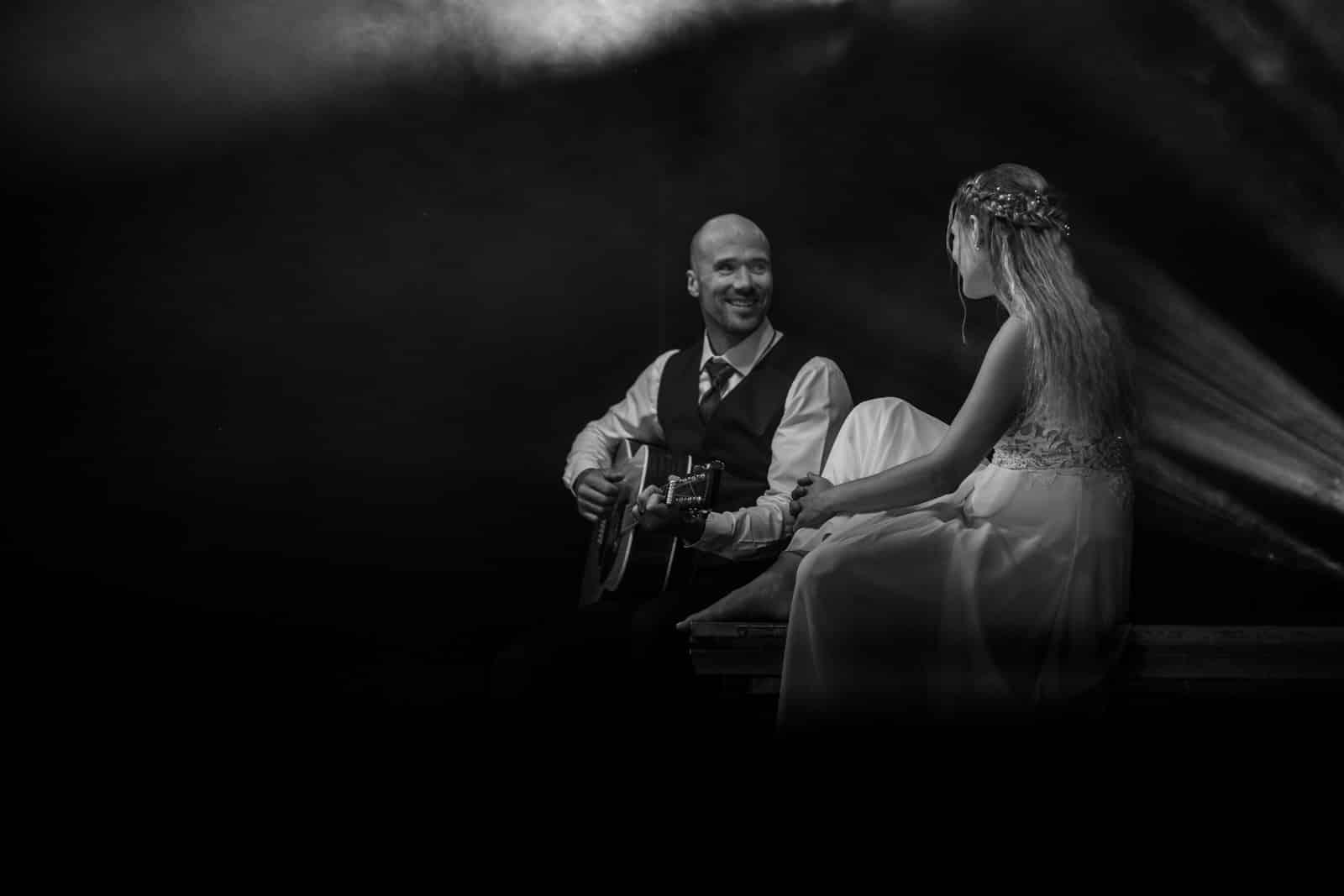 Bräutigam spielt auf einer Bühne ein Lied für seine Braut.