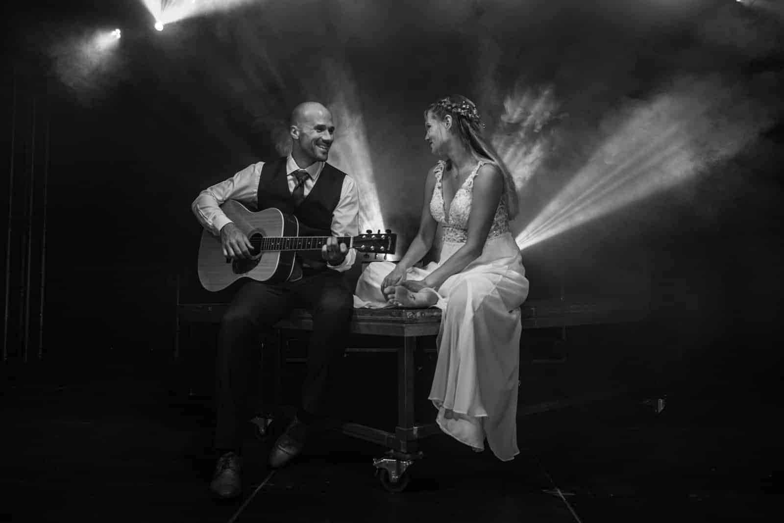 Brautpaar sitzt auf einer Bühne und der Bräutigam spielt Gitarre, Braut hört zu.