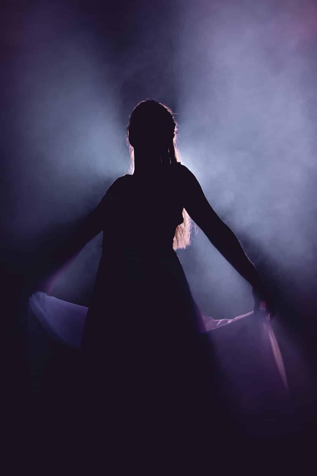 Braut steht im Schatten eines Scheinwerfers und hält ihr Kleid an der linken und rechten Seite hoch.