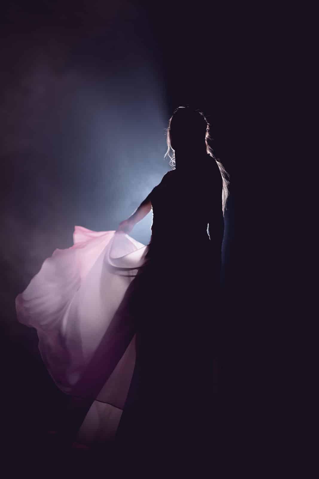 Braut wirft im Schatten des Scheinwerferlichts ihr Kleid hoch.