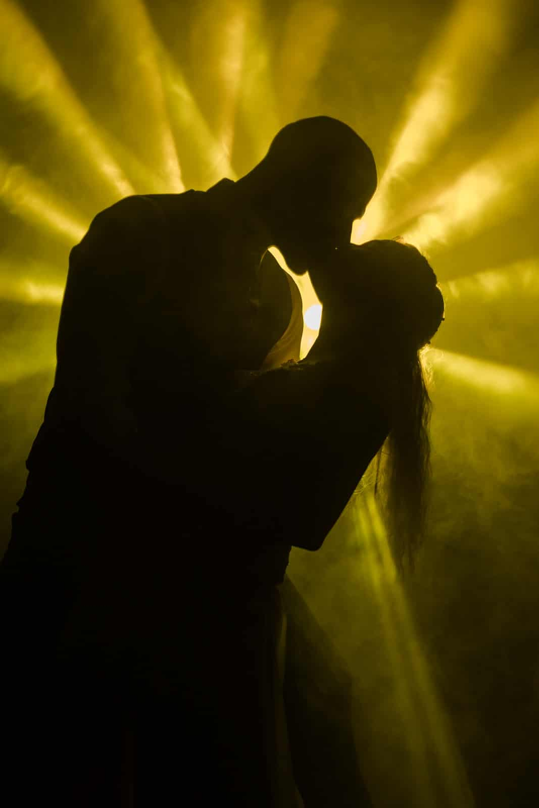 Brautpaar steht im schein eines gelben Scheinwerfers und die beiden Küssen sich als Silhouette