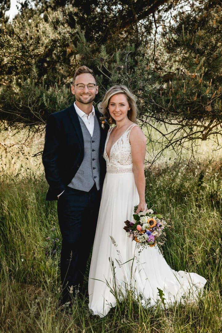 Brautpaar steht auf Wiese unter einem Baum und lacht in die Kamera in Griesheim