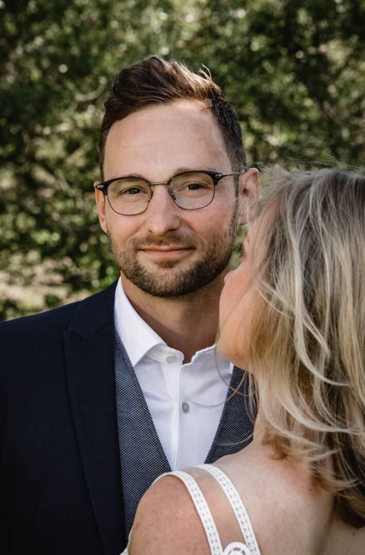 Bräutigam schaut beim Portraitshooting über die Schulter seiner Braut in die Kamera