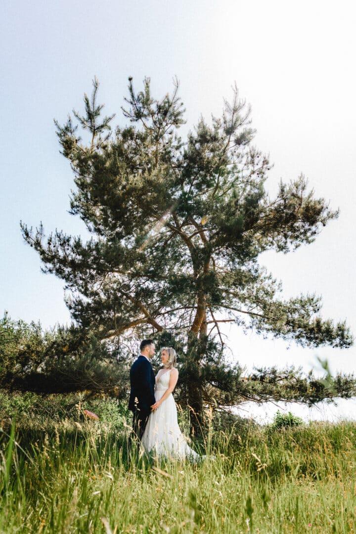 Brautpaar steht in Portraitshooting unter einem Baum auf einer grünen Wiese