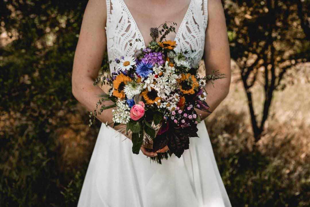 Brautstrauss einer Vintagebraut in den Griesheimer Dünen mit Sonnenblumen und Kornblumen und Margeriten