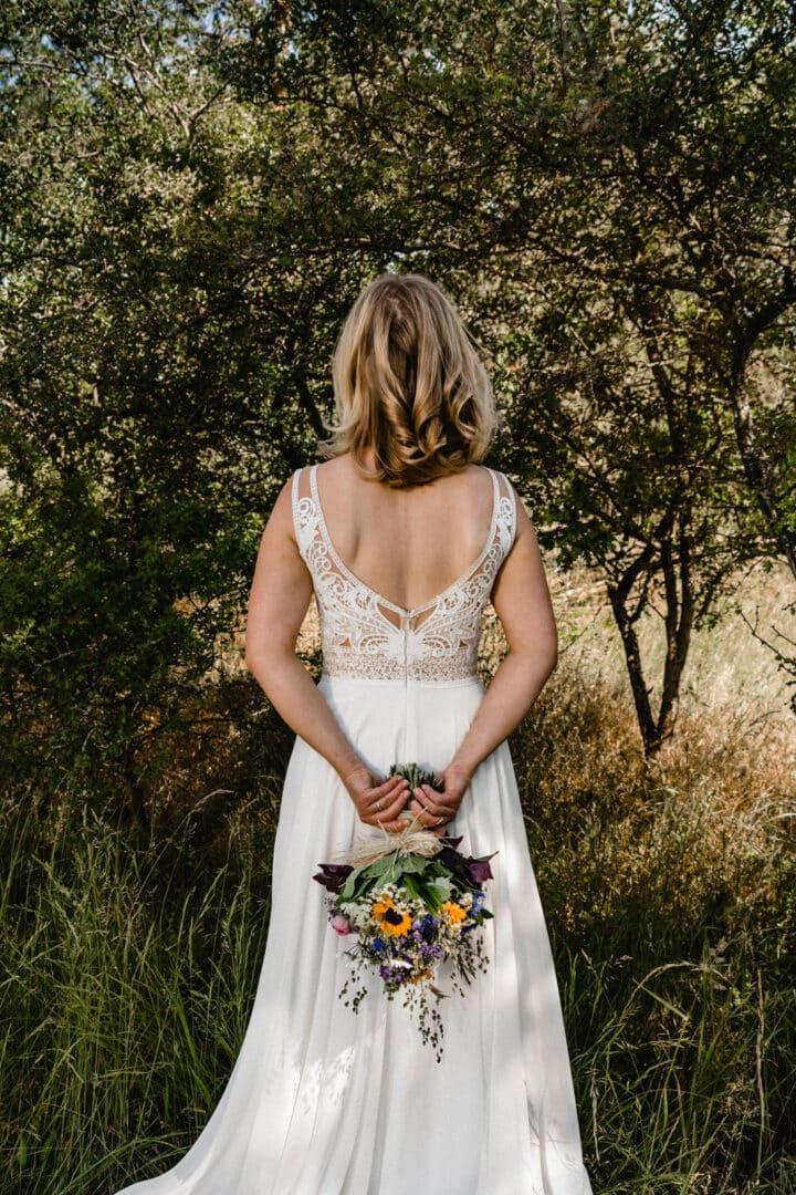 Braut beim Portraitshooting von hinten mit Brautstrauss und schönem freien Rücken