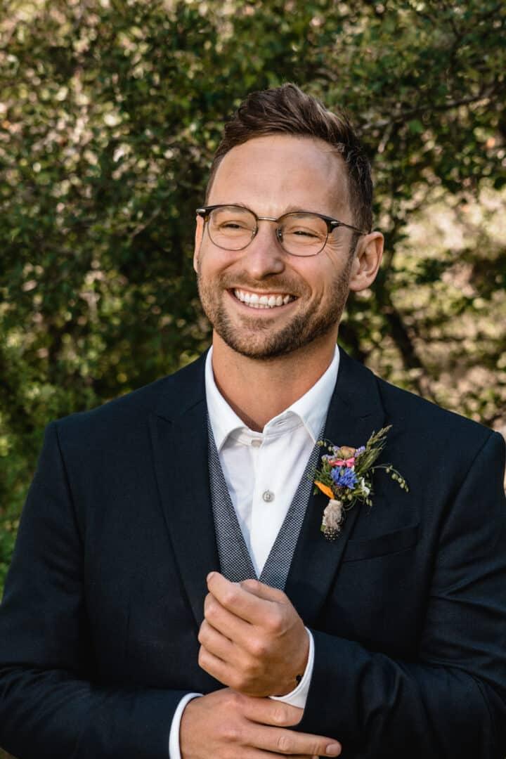 Bräutigam beim Portraitshooting lacht und richtet sich den Manschettenknopf