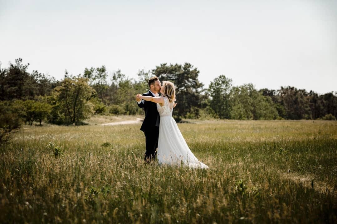 Brautpaar steht auf Wiese und hält die Arme ausgestreckt und kuesst sich