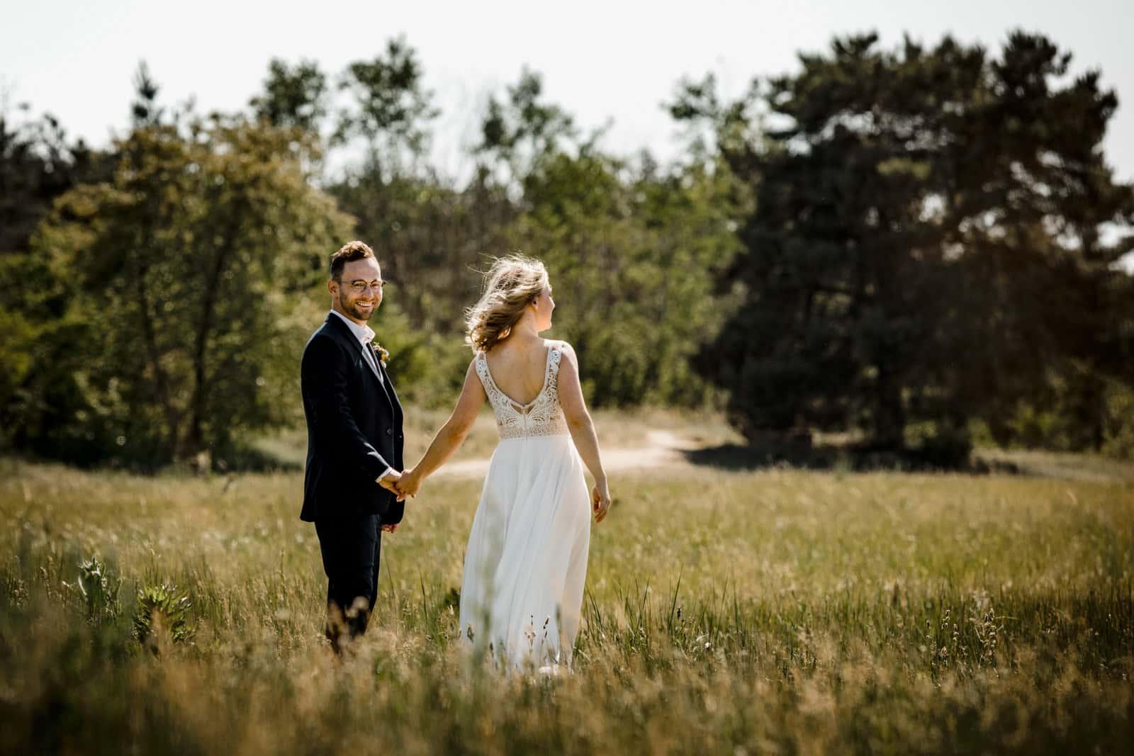Braut und Bräutigam stehen auf Wiese und halten Hand und Bräutigam lacht in Kamera