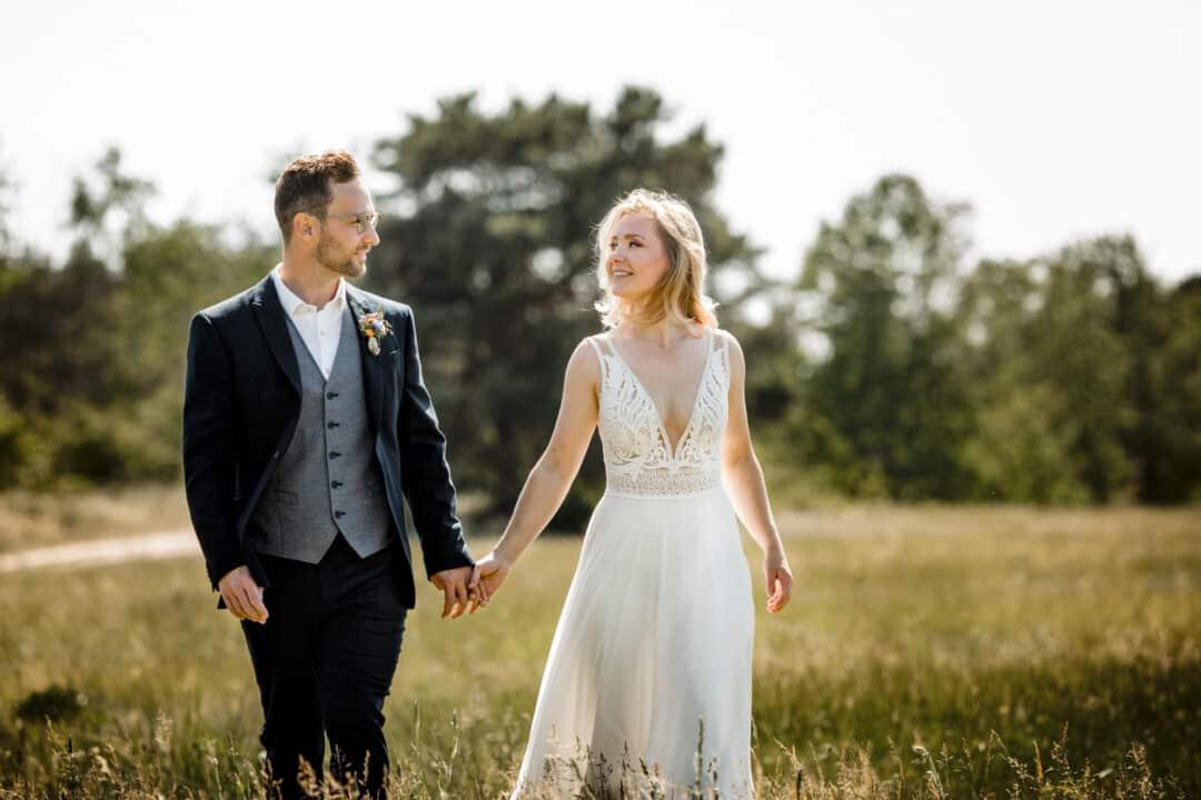 Braut und Bräutigam laufen Hand in Hand über eine Wiese im Sommer bei Sonnenschein und lachen sich an.