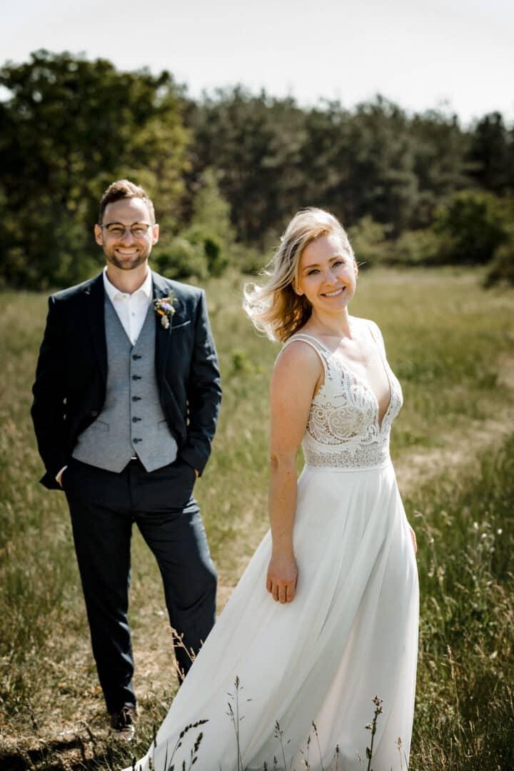 Braut lacht im Vordergrund mit Bräutigam im Hintergrund beim Outdoor Brautpaarshooting in den Griesheimer Dünen