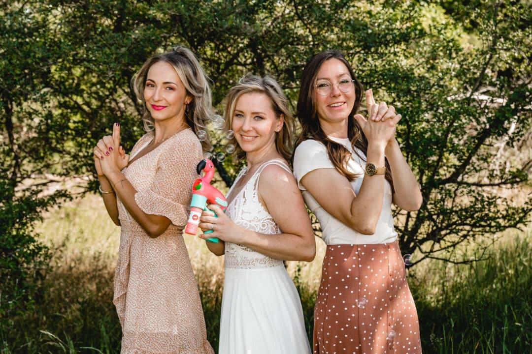 Braut und ihre zwei Trauzeuginnen posen outdoor mit einer Flamingo Seifenblasenmaschine als Charlies Angels.