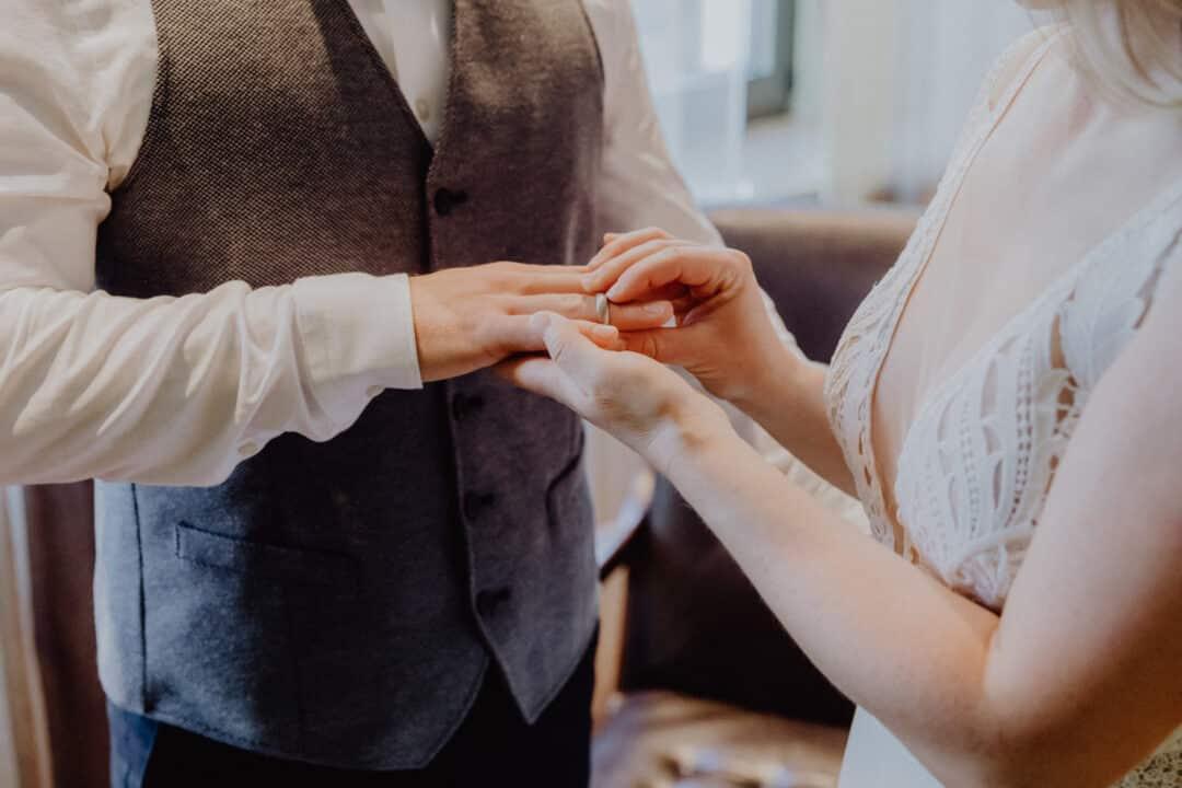 Braut steckt ihrem Bräutigam den Ring an in einer bunten Großaufnahme im Standesamt Griesheim