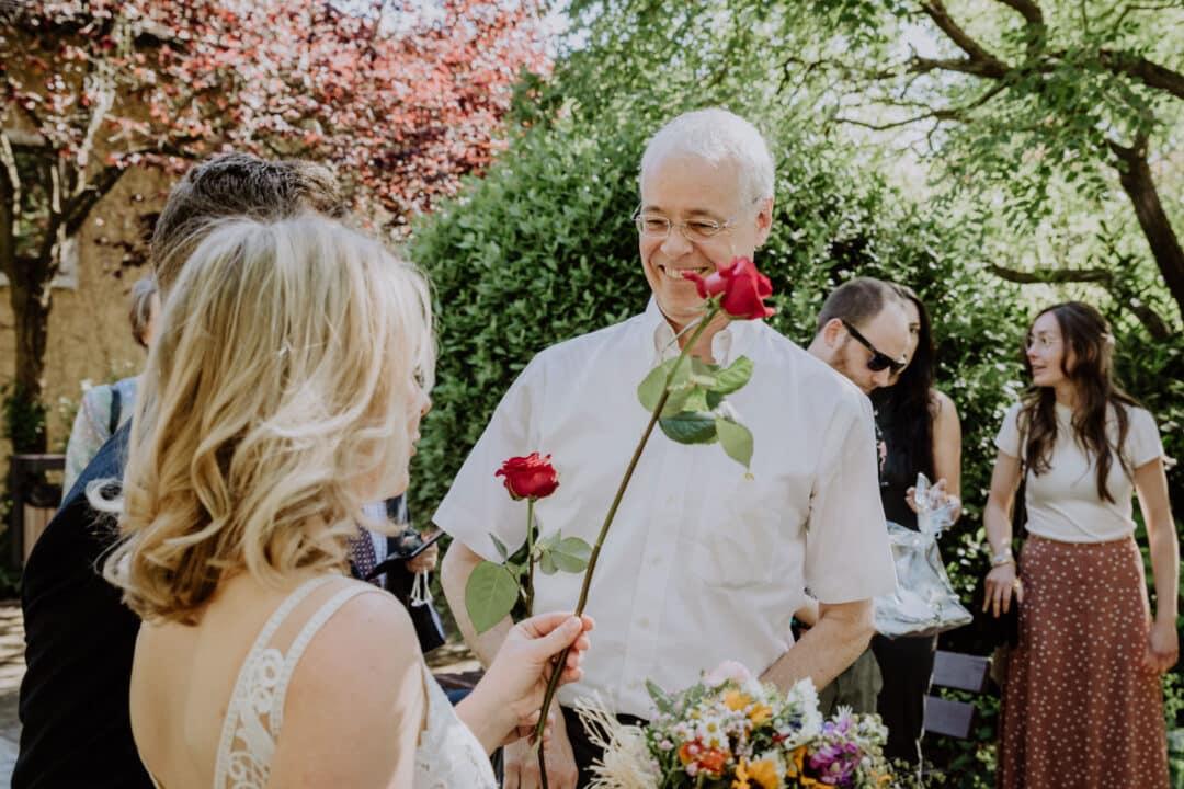 Ein Mann gratuliert mit Rosen dem Brautpaar nach der Trauung im Standesamt in Griesheim